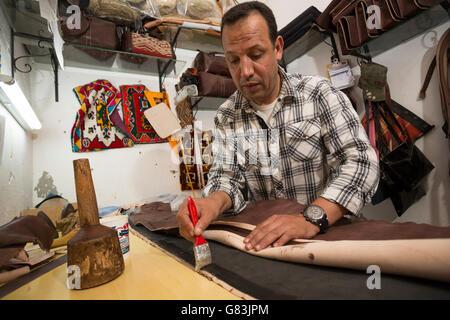 Un artisanat du cuir dans son atelier de la médina de Marrakech, Maroc. Banque D'Images