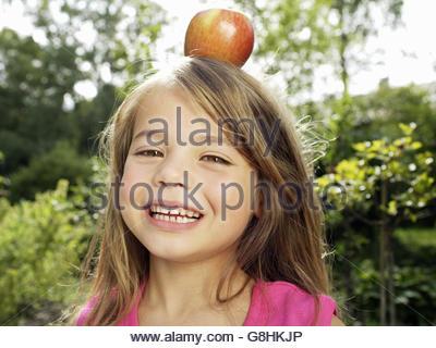 Jeune fille sur la tête d'apple d'équilibrage Banque D'Images