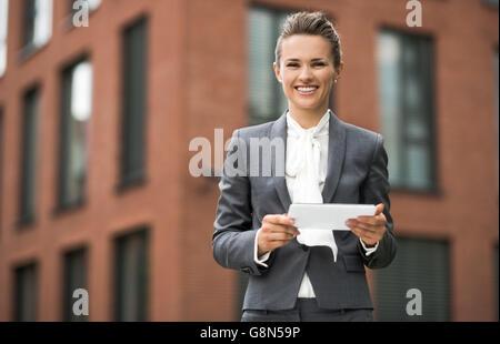 La nouvelle entreprise. Moderne Smiling business woman using tablet PC contre l'immeuble de bureaux