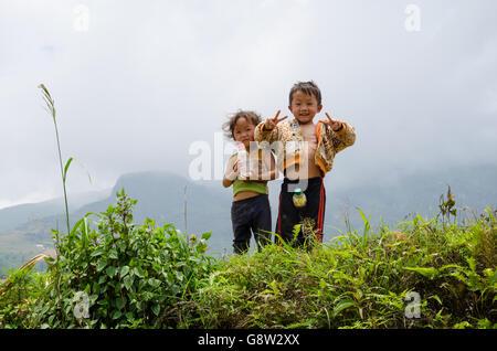 Deux jeunes enfants vietnamiens au Vietnam du Nord campagne dire bonjour et faire le signe v part en face de l'appareil Banque D'Images