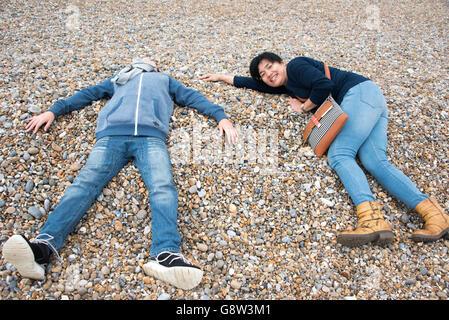 Garçon et la femme portant sur une plage de galets Banque D'Images