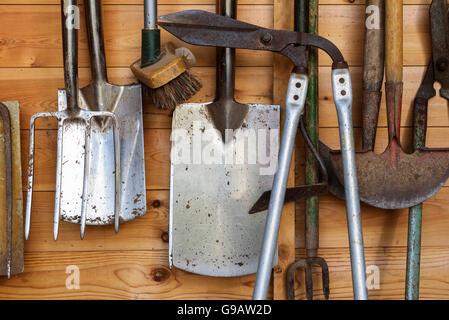 Outils de jardin suspendu dans une cabane en bois. Banque D'Images