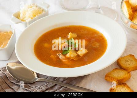 Une assiette de soupe de poissons et fruits de mer français, servi avec du pain grillé, sauce rouille et de fromage Banque D'Images