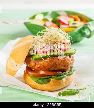 Un délicieux hamburger gastronomique avec des légumes frais: tomate, épinards, choux, radis et cornichons Banque D'Images