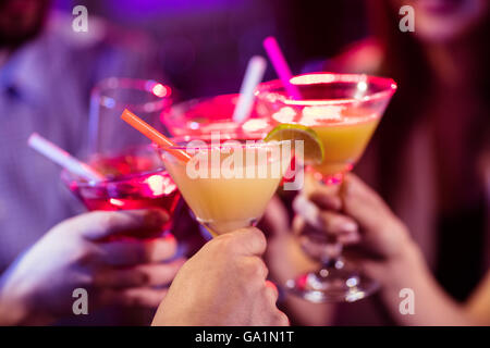 Groupe d'amis toasting cocktails au bar Banque D'Images