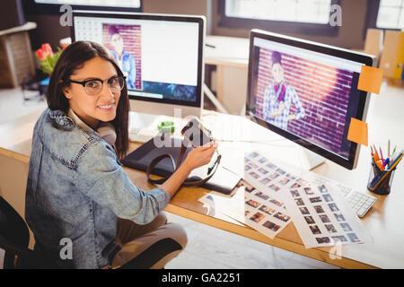 Graphic Designer holding digital camera
