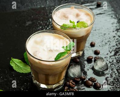 Café glacé dans des verres avec des glaçons et des feuilles de menthe fraîche et les grains de café Banque D'Images