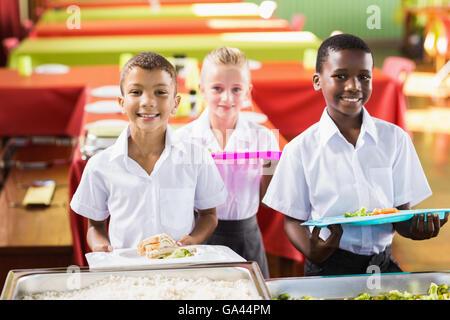 Student holding food bac dans la cafétéria de l'école Banque D'Images