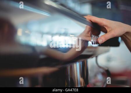 Close-up de barista de pousser sur le bouton au café cafétéria Banque D'Images