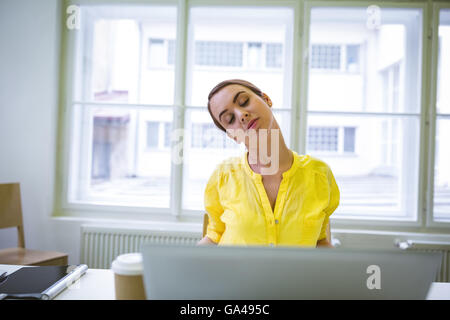 Businesswoman stretching in creative office Banque D'Images