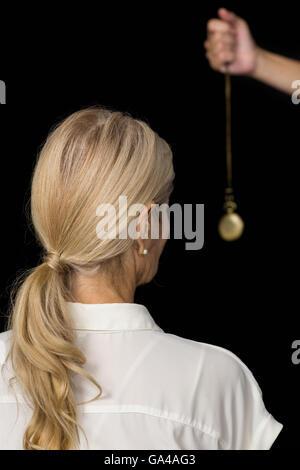 La main coupée de l'hypnothérapeute holding pendulum par femme Banque D'Images