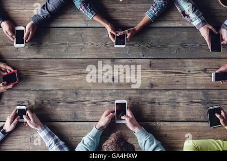 Hipster des gens assis autour de la table avec les smartphones Banque D'Images