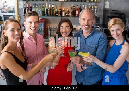 Groupe d'amis toasting verres de cocktail Banque D'Images