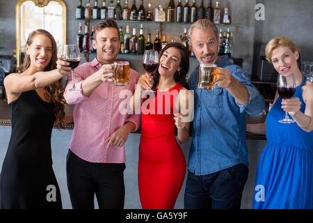 Groupe d'amis holding verres de bière et vin Banque D'Images
