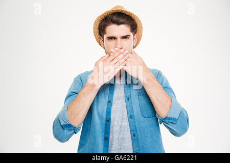 Beau jeune homme en chemise bleu et un chapeau couvrait sa bouche par les mains sur fond blanc Banque D'Images