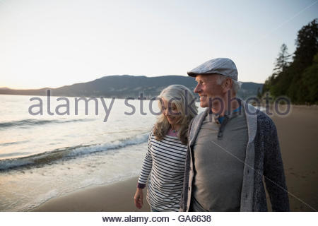 Senior couple walking on beach at sunset Banque D'Images