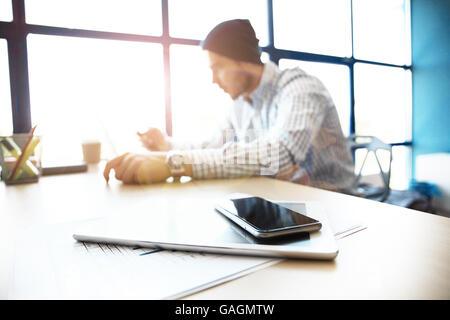Travail de bureau avec ordinateur portable sur la table de bois à l'encontre de windows. Banque D'Images
