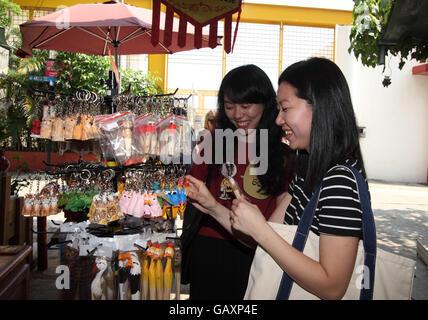 Deux jeunes femmes chinoises sourire alors qu'ils se regardent dans une boutique de souvenirs au Stanley Market. Banque D'Images