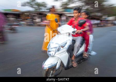 Jeune couple sur cyclomoteur dans Paud village près de Pune, Maharashtra, Inde. Motion Blur Flash. Banque D'Images