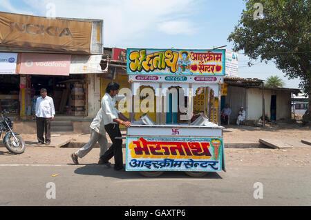 Paud village près de Pune, Maharashtra, Inde. Hommes poussent une cabine de glace mobile le long de la rue. Banque D'Images