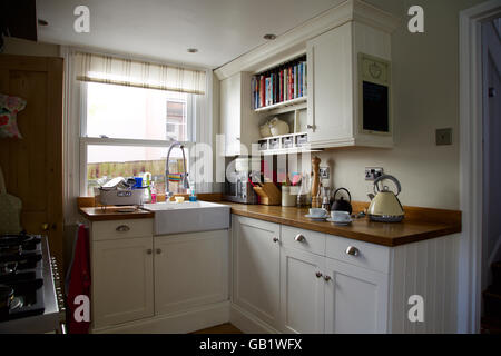 Coin cuisine victorienne avec fenêtre dans la vraie maison familiale électrique plateau tasse pot Crème lavabo placards Banque D'Images