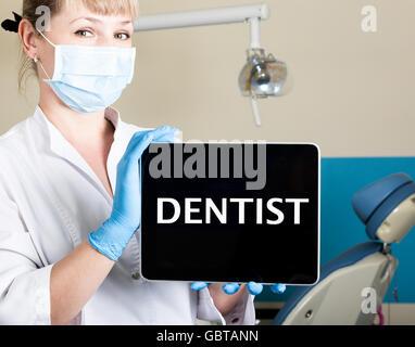 La technologie, internet et la mise en réseau en medicine concept - Dentiste femail holding a tablet pc avec dentiste signe. à l'arrière-plan de l'équipement dentaire Banque D'Images