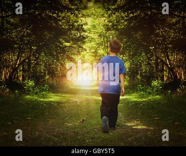 Un enfant marche dans les bois sombres en une lumière vive sur un chemin pour la liberté ou le bonheur d'un concept. Banque D'Images