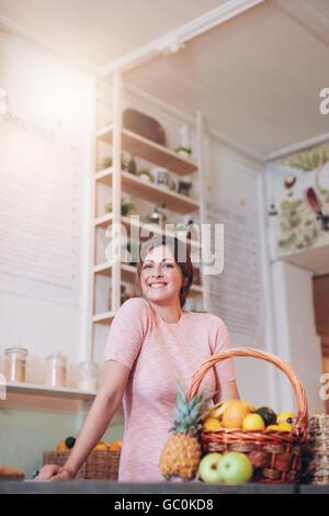 Smiling bar à jus propriétaire debout derrière le comptoir et à la recherche à l'appareil photo. Portrait jeune Banque D'Images