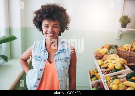 Portrait of happy young bar à jus propriétaire à la caméra et au sourire. Modèle féminin africain par permanent plateau de fruits dans le café.