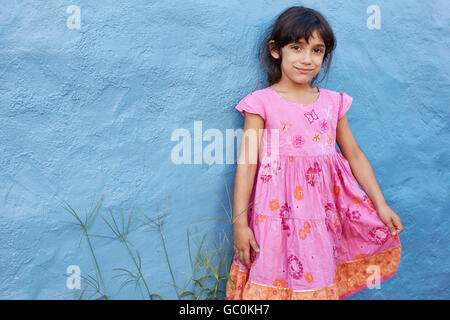 Shot of cute little girl in belle robe rose looking at camera while standing contre mur bleu. Banque D'Images