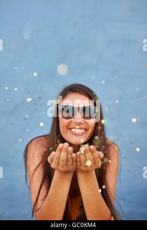 Shot of young woman blowing sparkles sur fond bleu. Caucasian female model blowing confetti dans l'air et smili Banque D'Images