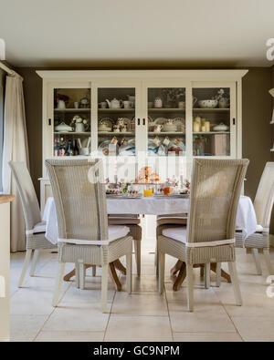 Fulham Lloyd Loom chaise de salle à manger autour de table les croissant. Une grande commode blanche se trouve dans Banque D'Images