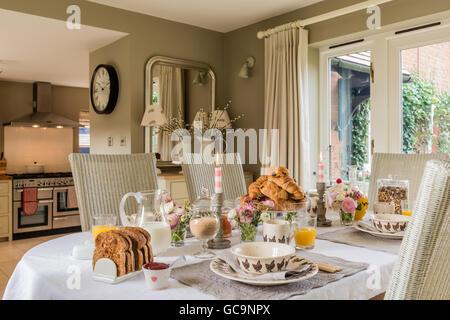 Table dressée avec petit déjeuner croissant et pain grillé. La chaise de salle à manger sont Fulham et Lloyd Loom. Banque D'Images