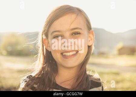 Belle brown-eyed girl smiling dans un champ ensoleillé.