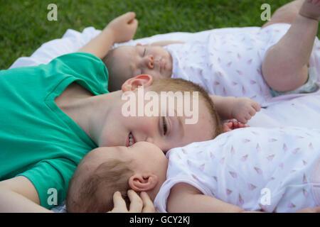 Heureux frère embrasser une de ses soeurs jumelles dans park Banque D'Images