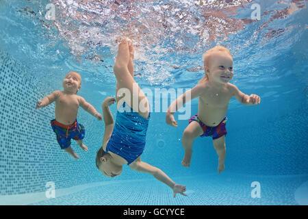 Funny photo de bébés actif nager et plonger avec plaisir - aller au fond avec des touches sous-marine dans la piscine. Banque D'Images