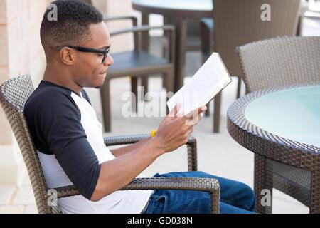 Closeup portrait, jeune homme ringard avec de grandes lunettes noires, s'asseoir et lire, isolé à l'extérieur arrière Banque D'Images