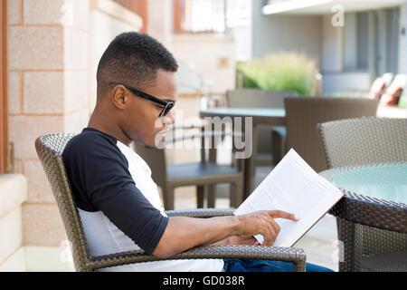 Closeup portrait, jeune homme ringard avec de grandes lunettes noires, s'asseoir et lire, isolé à l'extérieur. fond Banque D'Images