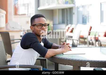 Closeup portrait, jeune homme ringard avec de grandes lunettes noires, de s'asseoir, de la rêverie sur le passé, Banque D'Images