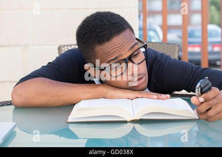 Closeup portrait nerdy, jeune homme dans de grandes lunettes noires holding watch, relevant très fatigué de la lecture, Banque D'Images
