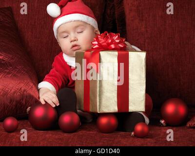 À l'âge de six mois, bébé garçon en costume Santa dormir avec un cadeau de Noël à ses genoux Banque D'Images