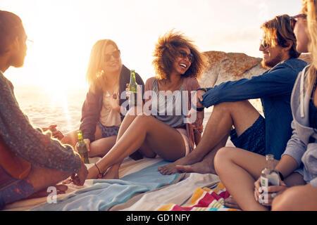 Mixed Race friends having fun at the beach. Groupe de jeunes heureux assis ensemble à la plage de parler et boire Banque D'Images