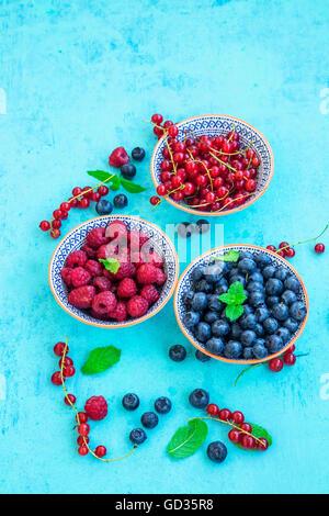 Fruits frais sain avec les feuilles de menthe dans des bols en bois peint Banque D'Images