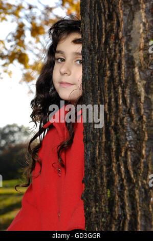Petite fille de cinq ans en manteau rouge près d'un arbre dans un parc Banque D'Images