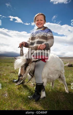 Fille assise sur une chèvre, dans l'ouest de l'Islande Banque D'Images