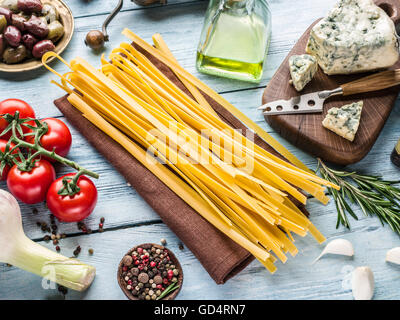 Ingrédients pâtes. Les tomates cerise, les pâtes spaghetti, de romarin et d'épices sur la table en bois. Banque D'Images