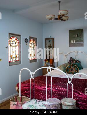 1930 vitraux de chambre avec cadre de lit en fer forgé et sari throw Banque D'Images
