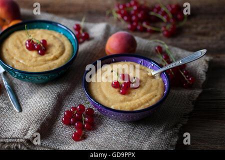 Vanille abricot pudding de millet dans deux petits bols et surmontées de groseille rouge Banque D'Images