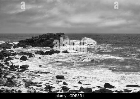 Briser les vagues dans l'épave de Porth, St Mary's, Îles Scilly, au Royaume-Uni. Version noir et blanc Banque D'Images