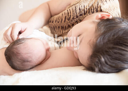 Mother lying on bed with newborn baby boy Banque D'Images
